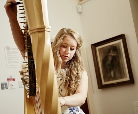 Student Mari Kelly tuning her harp before playing at the WHC launch